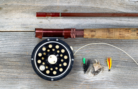 fishing rod: Antique fly fishing reel and rod on rustic wood. Layout in horizontal format.