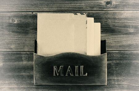 old envelope: Vintage concept of an old metal mailbox with letters inside on rustic wood