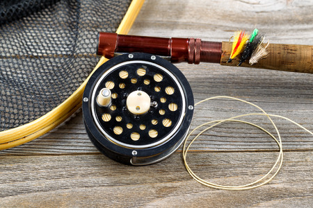 Close up of an antique fly fishing reel, rod, landing net and artificial flies on rustic wood. Layout in horizontal format.