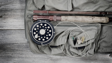 fishing equipment: Vintage concept of an antique fly fishing reel and rod with vest and flies on rustic wood. Layout in horizontal format. Stock Photo