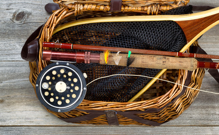 Antique fly fishing reel, rod, flies, and net on top of open creel with rustic wood underneath. Layout in horizontal format. Stockfoto