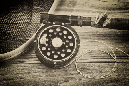 Vintage concept with grain of an antique fly fishing reel, rod, landing net and artificial flies on rustic wood. Close up with layout in horizontal format.