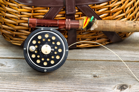 Close up of an antique fly fishing reel, rod, and artificial flies in front of creel with rustic wood underneath. Layout in horizontal format. Stockfoto