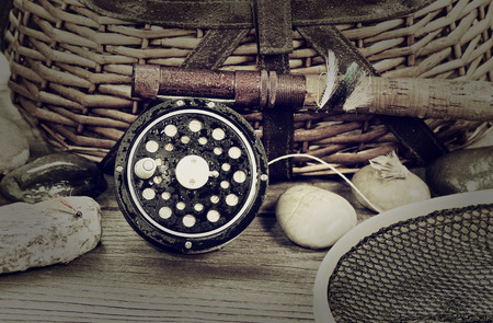 Vintage concept with grain of a wet antique fly fishing reel, rod, landing net, artificial flies and rocks in front of creel with rustic wood underneath. Layout in horizontal format.