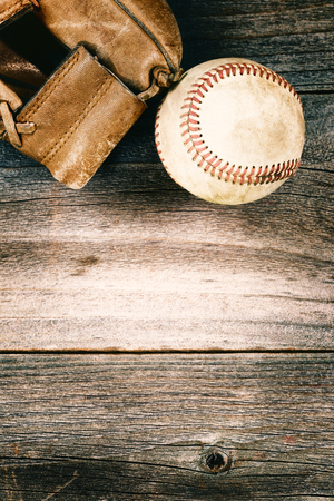 mitt: Vintage concept of an old baseball and weathered leather mitt on rustic wood. Format in vertical layout.