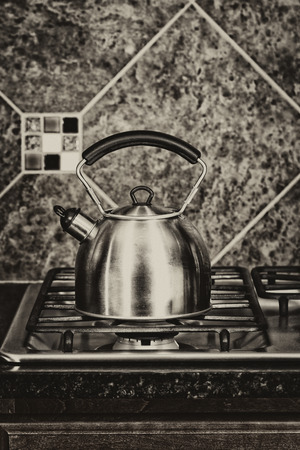 splash back: Vintage concept of a stainless steel tea pot on stove top.