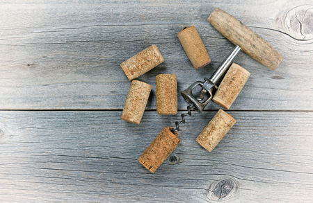 cork: Vintage concept of several used wine corks and opener on rustic wooden boards.