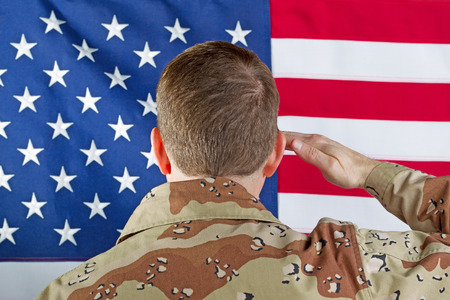 Close up image male soldier, back to camera, saluting United States of America flag while indoors not wearing hear gear.