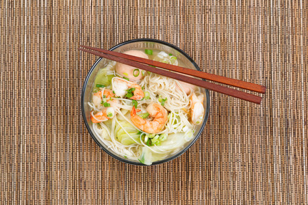 chinese noodle: Top view image of Chinese noodle soup in clear glass bowl on top of natural bamboo placemat. Layout in horizontal format. Stock Photo