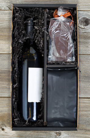 Vertical image of a gift box with wine, chocolate and bag of coffee on top of rustic wood.