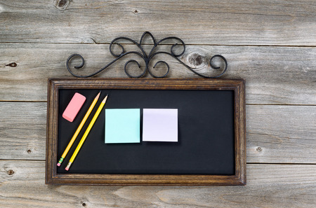 antique sleigh: Old fashion chalkboard, pencils, eraser and paper notes on rustic wood. Layout in horizontal format.