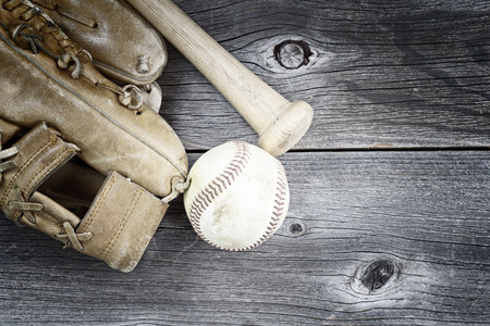 guante beisbol: Vintage concept of  old worn glove, bat and used baseball on rustic wood Foto de archivo
