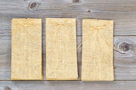 angled view: Overhead angled view of three burlap bags on rustic wood.