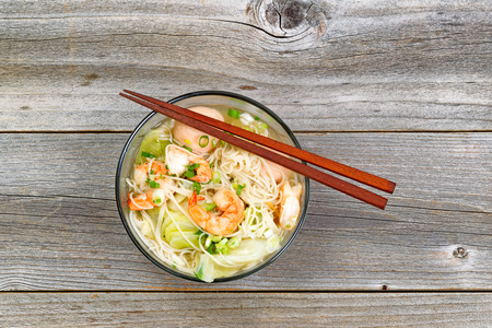 chinese noodle: Top view image of Chinese noodle soup in clear glass bowl on top of rustic wood. Layout in horizontal format.