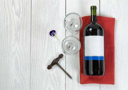 angled view: Overhead angled view of a large bottle of red wine, drinking glasses, serving napkin, flower and antique corkscrew on white wooden boards.