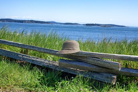 split rail: Image of a leisure hat resting on rustic wooden split rail fence with ocean and sky in background. Stock Photo