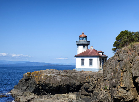 puget sound: Lighthouse on the Puget Sound of Washington state during nice day with blue sky and clouds.