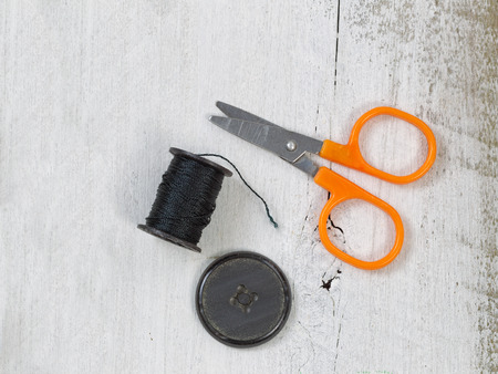 Top view of a spool of used black thread scissors and button resting on rustic white wood. Stock Photo