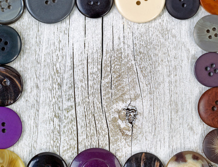 clothing buttons: Top view of a clothing buttons in different sizes and colors forming border on rustic white wood. Stock Photo