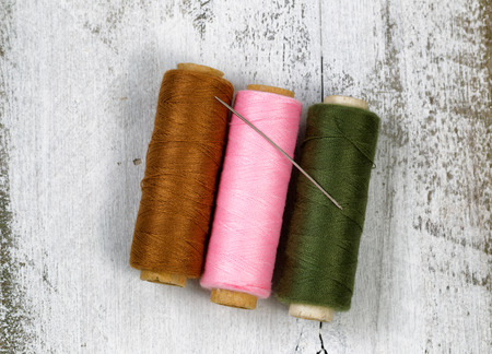 Three spools of different colors of thread with single needle on top of rustic white wood.