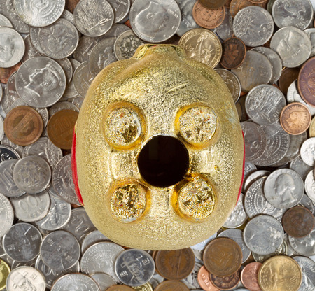 hard times: Close up of upside down piggy bank focus on complete belly with loose coins underneath. Concept of financial hard times.