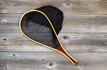 trout fishing: Landing net for trout fishing on rustic wooden boards.