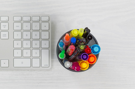 Container of pens and markers focus top of container and computer keyboard on rustic white desktop.