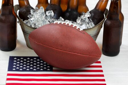 pigskin: Close up of American football ice cold beer in bucket and flag with rustic white wood underneath. Perfect for the Fourth of July holiday. Filled frame in horizontal format.