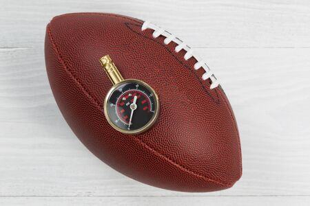 air pressure: Close up of America football with air pressure gauge on top of ball with rustic white wood underneath.