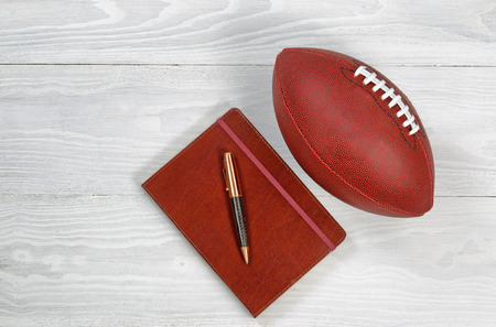 schemes: Image of executive notepad pen and American football on white rustic wood. Playbook concept for game plan.