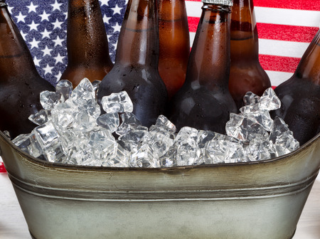 Close up of cold beer and ice in steel tub with American flag in background. Fourth of July holiday concept.