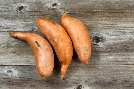 unclean: High angle view of three unclean yams on rustic wood. Layout in horizontal format.