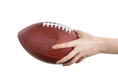 holding close: Female hand holding American football on isolated white background. Stock Photo