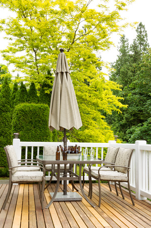 bottled beer: Vertical photo of outdoor patio table with cold bottled beer in bucket and drinking glasses on cedar wood patio. Colorful trees in background.