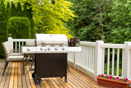 Photo of clean barbecue cooker with cold beer in bucket on cedar deck. Table and colorful trees in background. Stock Photo