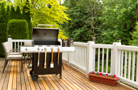 grill: Photo of a clean barbecue cooker with cookware and cold beer in bucket on cedar wood patio. Table and colorful trees in background.