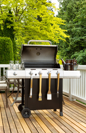 Vertical photo of an open barbecue cooker with cookware and cold beer in bucket on cedar wood patio. Table and colorful trees in background. Stockfoto