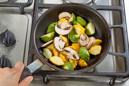 close up food: Close up of hand holding frying pan, focus on food, while cooking vegetables in pan on top of stove.