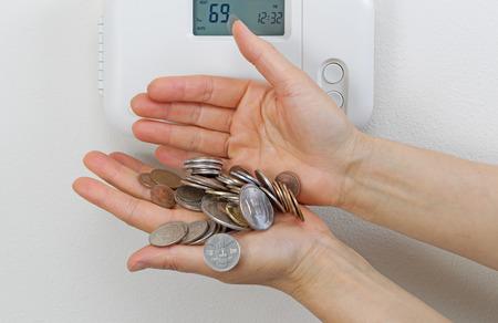 factura: Primer plano de las manos femeninas derramar dinero debido a los costos de calefacción. La pérdida financiera del concepto de dinero. Foto de archivo
