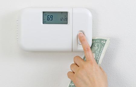 dinero: Primer plano de la mano femenina ajustando casa termostato de la calefacción con el dinero en moneda parcial en la palma de la mano.