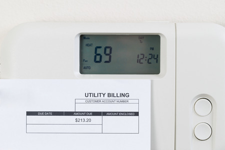 utility: Close up of home heating thermostat with partial utility bill on wall. Stock Photo