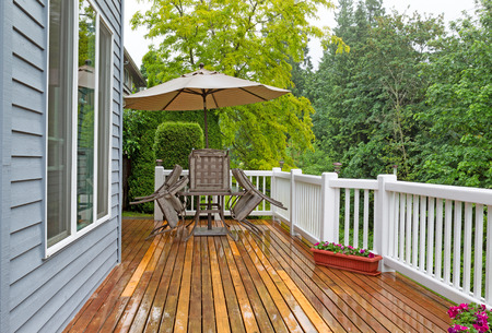porches: Horizontal photo of outdoor patio furniture put away due to poor weather. Photo taken during heavy rain on cedar wood deck. Stock Photo