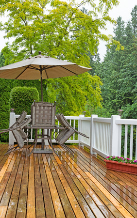 put away: Vertical photo of outdoor patio furniture put away due to poor weather. Heavy rain on cedar wood deck.