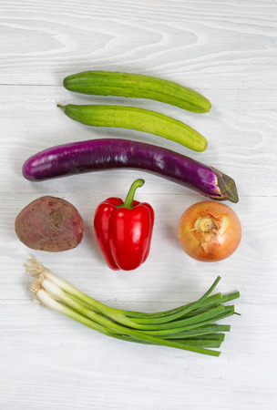 red pepper: Top view angle shot of fresh vegetables consisting of beet green onion yellow onion red bell pepper eggplant and cucumber on white wood. Layout in vertical format.