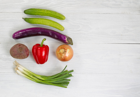 onion: Top view angle shot of fresh vegetables consisting of beet green onion yellow onion red bell pepper eggplant and cucumber on white wood. Layout in horizontal format with plenty of copy space. Stock Photo