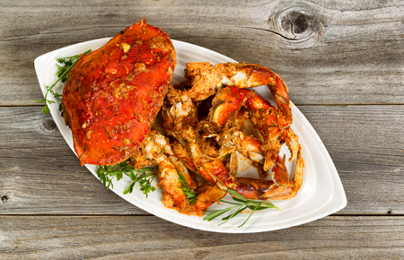 angled view: High angled view of freshly cooked crab with spicy sauce and herbs on white serving plate. Rustic wood underneath dish.