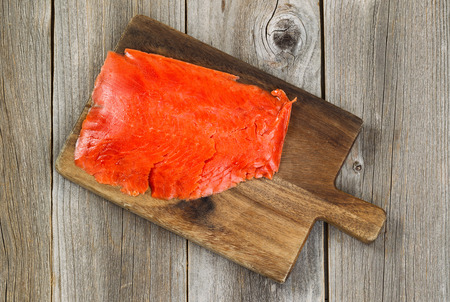 red salmon: Top view of thinly sliced cold smoked red salmon on wooden server board with rustic wood underneath. Stock Photo