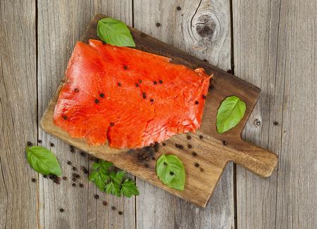 salmon ahumado: Vista superior de rodajas finas de salmón rojo ahumado en frío, junto con hierbas y condimentos en placa de servidor de madera. Madera rústica debajo.