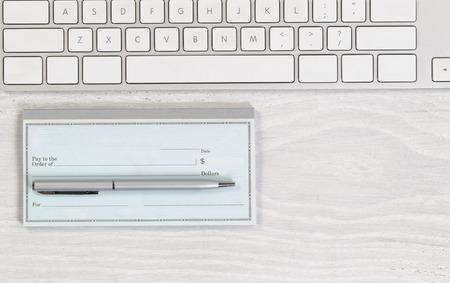 chequera: Imagen del teclado parcial con chequera en blanco y pluma de plata en el escritorio blanco. Disposición en formato horizontal.
