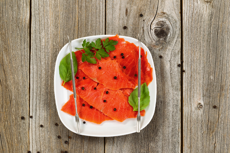 High angled shot of thinly sliced cold smoked red salmon with herbs and seasoning in white plate. Rustic wood underneath.